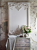 White, decorative, carved panel on wall behind bouquet of roses and bolt of embroidered fabric on chest of drawers delicately painted in soft colours