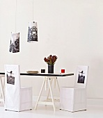 Dining table on trestles, chairs with printed loose covers and lampshades with similar designs