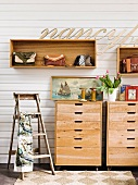Vintage-style hall decor - lettering above handbags in wall-mounted shelving units; old, painter's stepladder and still-life arrangement on wooden chests of drawers
