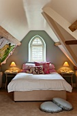 Stacked scatter cushions on double bed below window in painted gable end of attic storey, romantic bedside lamps and round cushions on floor