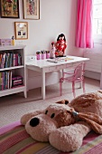 Pink Philippe Starck ghost chair at a desk in a girls bedroom