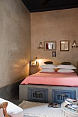 Mirrors above bed with storage compatments and lit bedside lamp in Moroccan home