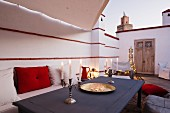 Lit candles and daybed on roof terrace of Marrakesh medina home