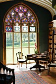 Detail of library in English stately home with view of summery parkland through large ecclesiastical window