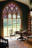 Bibliotheksausschnitt eines englischen Anwesens mit Blick durch das sakrale große Fenster in die sommerliche Parkanlage