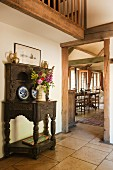 Ornaments on antique dresser in foyer of simple English country house with gallery, exposed beams and view into bright dining area