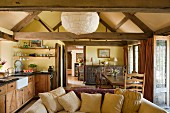 View from kitchen-dining area into foyer of simple English country house with exposed timber structure; comfortable sofa with many scatter cushions in foreground