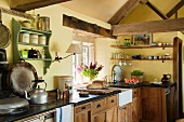 Corner of rustic kitchen in English country house with exposed timber structure, antique cooker and shelves of crockery and glasses