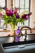 China sink in stone worksurface with nostalgic tap fittings; summery bouquet in front of window