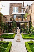 Symmetrically designed courtyard with a statue, boxwood hedge and paved walkway