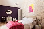 Schlafzimmer mit Sputnik- Deckenleuchte und buntem Pop-Art-Bild an Natursteinwand
