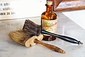 Old barbers' brushes next to apothecary bottle