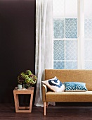 Modern wooden side table with a bouquet of flowers next to a 50's style sofa in front of a window with a curtain made of airy fabric