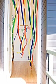 Children's birthday party - view through an open door of a colorful streamers hanging from the ceiling and birthday garland