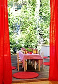 A red curtain has opened to reveal a children's party - decorated table with small wooden chairs on a terrace
