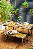Tiled patio with dining table and benches; in the background a white box with bamboo plants and hanging plant pots