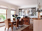 Wicker chairs with tall backrests around classic dining table; wood-clad breakfast bar to one side