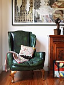 Wing-back armchair with green leather cover next to cabinet and contemporary artworks