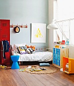 Young boy's room with bed, red locker and commode with colorful drawers