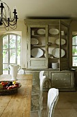 Distressed crockery cabinet with open back door and wooden kitchen table in Provence country house