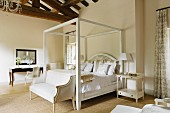 White four poster bed below high beamed ceiling of Provence country house