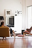 Corner of living room with TV in white-painted TV cupboard element beyond woman sitting on fifties-style seating