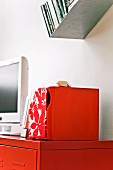 White TV and floral box on red-painted sideboard below angled, metal floating shelf of DVDs