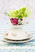 Hydrangea flowers and green hazel nuts in a tower made from an ornamental cup, saucer and plate