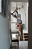 Mounted antlers double up as a hat rack on the wall of a landing with wooden balustrade