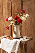 Red and white ranunculus in a pitcher