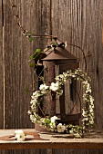 Heart-shaped wreath with white flowers by a rusty lantern