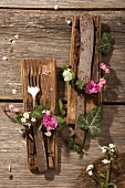 Old cutlery with ivy wreaths on tree bark