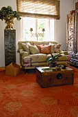 Trunk in front of sofa below window next to flower arrangement on plinth on carpet with Oriental pattern