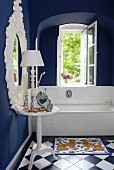Traditional bathroom in blue and white - white tiled bathtub below open window with view of garden in dark blue painted bathroom