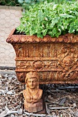 Antique flower trough on metal feet with a small bust of woman as decoration