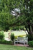 Holzbank im schlichten Landhausstil und Buchseinfassungen in romantischem Schlosspark; antike Amphoren im Hintergrund