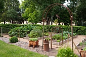Kitchen garden with vegetable beds - integrated into an historic garden but separated with wire mesh and antique archway