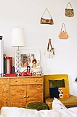 Japanese dolls and lamp with lampshade on retro sideboard next to chair below handbags hanging on wall