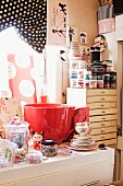 Oversized red teacup, tea service and Oriental doll on surface with sewing utensils in storage jars in background on chest of shallow drawers