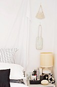 Draped curtain at head of bed and handbags hanging on wall above bedside table in bedroom