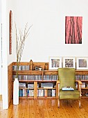 Large CD collection and books on pale wooden shelving behind comfortable vintage reading chair on castors