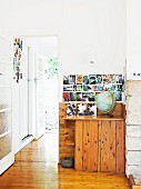 Collection of photos on wall in corner of room with rustic corner cupboard
