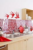 Psychedelic pattern on a red and white back splash above a kitchen sink with swallow wall decals on the white walls