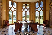 Marble and oak round table by Zervaco in octagonal dining room with marble flooring and italian woven leather chairs