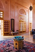Türkise Schale auf Holzhocker und orientalischer Teppich in hohem, rosa getöntem Salon mit Flügeltüren und halbkreisförmigem Ornament in Wand