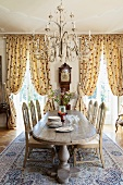 Magnificent dining room with solid wooden dining table below pretty chandelier; gathered, floor-length curtains in background at windows with view of park