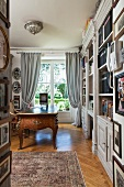 Grand wooden library with antique desk in front of floor-to-ceiling window with gathered silk curtains