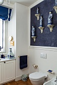 Corner of bright bathroom with collection of Chinese porcelain figurines on blue wall