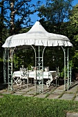Climber-covered garden pavilion with white roof above set dining table and chairs in sunlight
