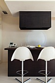 Minimalist, black kitchen counter with white bar stools